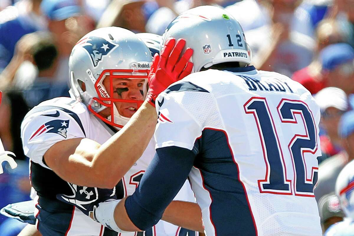Patriots wideout Julian Edelman, left, celebrates with Tom Brady after catching a touchdown pass in the first half Sunday.