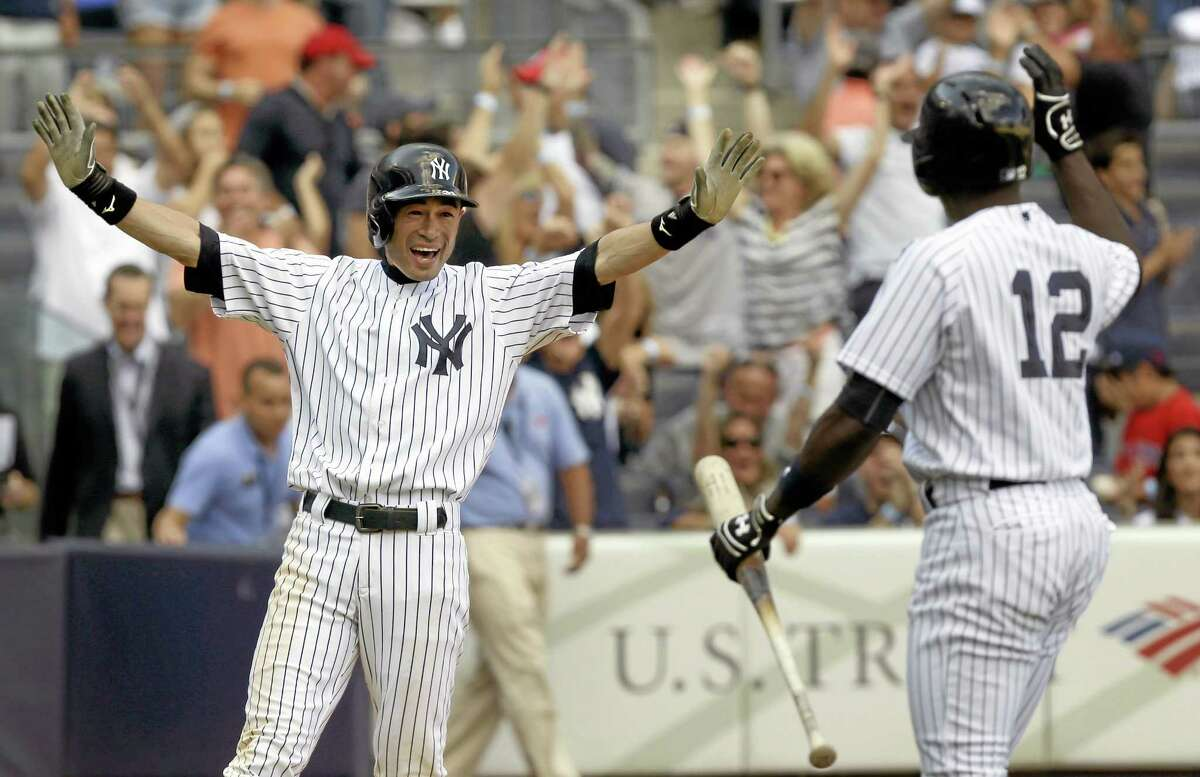 The Yankees' Ichiro Suzuki, left, reacts after scoring on a wild pitch to beat the Red Sox on Sunday.