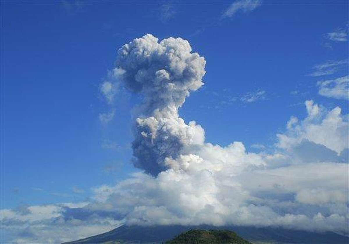 A cloud of volcanic ash shoots up to the sky as Mayon volcano, one of the Philippines' most active volcanoes, erupts after daybreak, viewed from Legazpi in Albay province in the central Philippines, Tuesday, May 7, 2013. At least five climbers were killed and more than a dozen others are trapped near the crater in its first eruption in three years, officials said. Rescue teams and helicopters were sent to Mayon volcano to bring out the dead. (AP Photo/Allan Imperial)