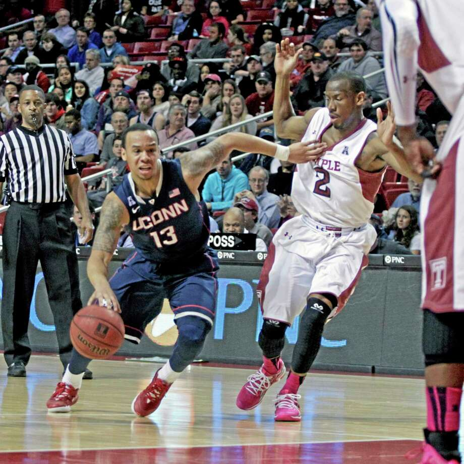 UConn's Shabazz Napier, left, drives against Temple's Will Cummings in the first half Thursday in Philadelphia. Photo: H. Rumph Jr. — The Associated Press  / FR61717 AP
