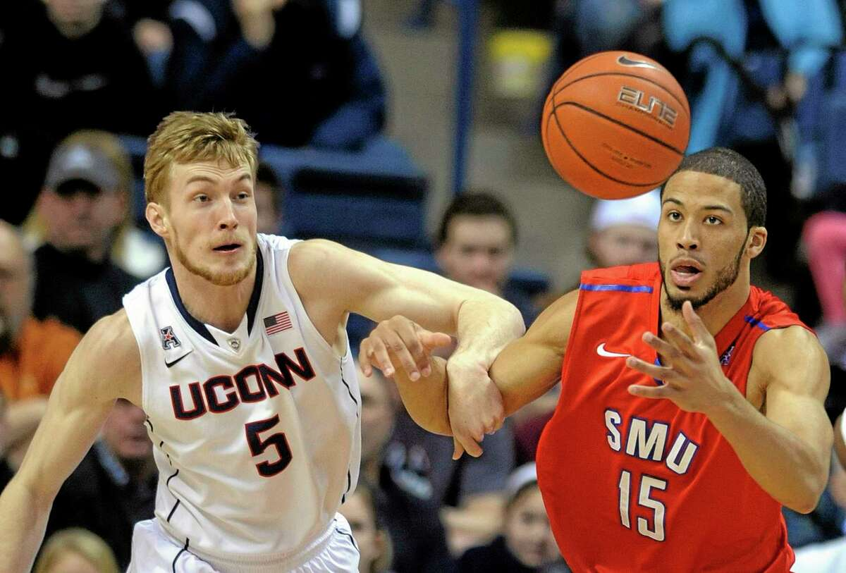 UConn's Niels Giffey and SMU's Cannen Cunningham fight for a loose ball during the first half of Sunday's game in Storrs.