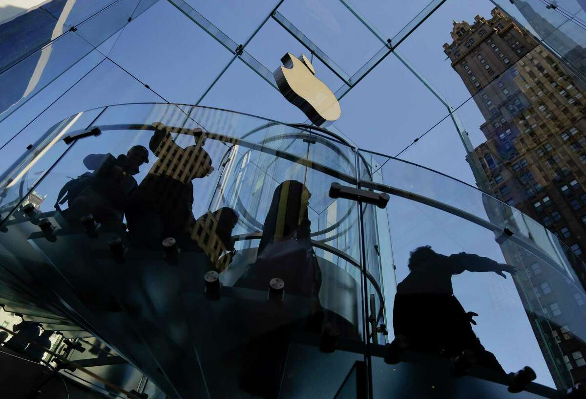 FILE - In this Friday, Sept. 19, 2014 file photo, a group of visitors to the Apple store descends a staircase to the showroom below to purchase the iPhone 6 and 6 Plus, in New York. The European Unionís competition watchdog is moving ahead with an inquiry of Apple's overseas tax practices, saying Ireland appears to grant the company illegal rebates that may have to be recouped. If the EUís preliminary finding were confirmed over the coming months, Apple Inc. could face a repayment bill worth billions of dollars because it funnels the bulk of its international sales through subsidiaries in Ireland, where it benefits from low, negotiated tax deals. (AP Photo/Julie Jacobson, file)