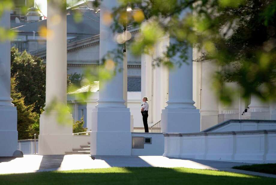 FILE - In this Sept. 22, 2014 file photo, a member of the Secret Service Uniformed Division looks out from the North Portico of the White House in Washington. Secret Service Director Julia Pierson said Tuesday the front door to the White House now locks automatically in a security breach. Pierson told a House panel that the switch to automatic locks at the White House's north door was made after an Army veteran jumped the fence on Sept. 19 and made his way into the interior of the building through two unlocked doors. (AP Photo/Carolyn Kaster, File) Photo: AP / AP