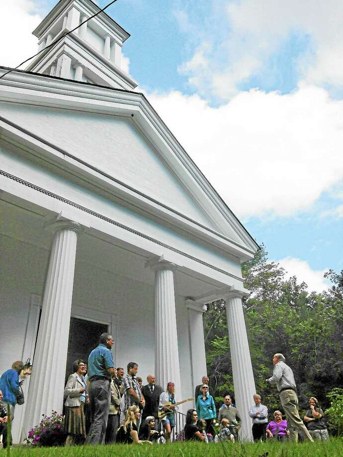 Church members stand on the green listening to Historical Society Member Paul Hart talk about Old Home Day at the First Congregational Church of Barkhamsted on Sunday afternoon. Photo: Mercy Quaye—Register Citizen
