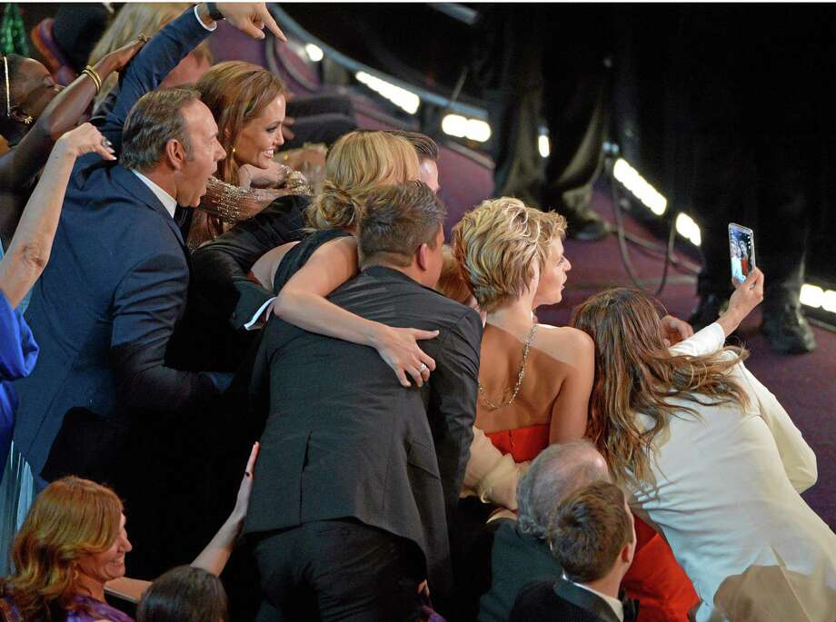 """Kevin Spacey, from left, Angelina Jolie, Julia Roberts, Brad Pitt, Jennifer Lawrence, Ellen Degeneres and Jared Leto join other celebrities for a """"selfie"""" during the Oscars at the Dolby Theatre on Sunday, March 2, 2014, in Los Angeles.  (Photo by John Shearer/Invision/AP) Photo: John Shearer/Invision/AP / Invision"""