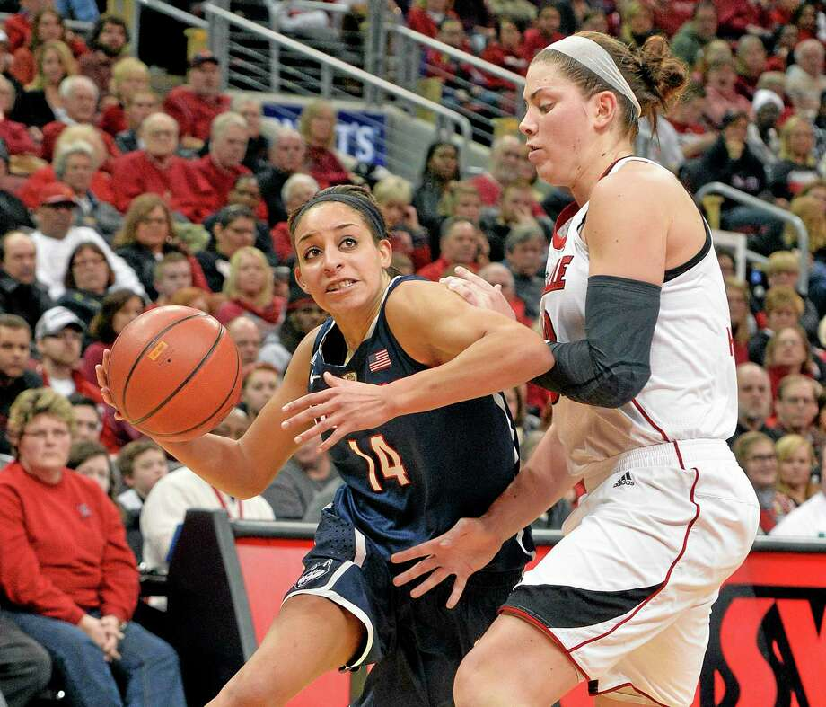 Timothy D. Easley — The Associated Press UConn's Bria Hartley, left, drives around Louisville's Sara Hammond during the second half Monday. Photo: AP / FR43398 AP