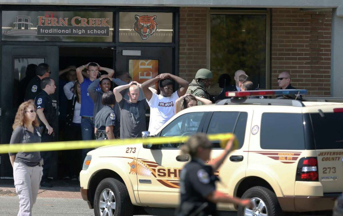 Students put their hands on their heads as they are lead out of Fern Creek High School in Louisville, Ky. on Tuesday, Sept. 30 2014 after a shooting.