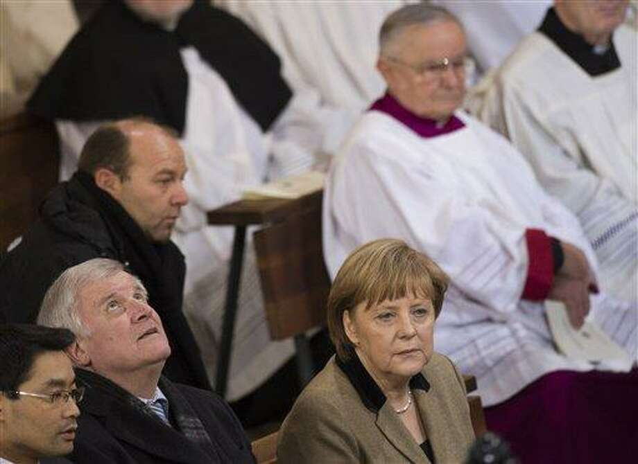 German Economy Minister Philipp Roesler, Bavarian state governor Horst Seehofer and German Chancellor Angela Merkel, bottom from left, attend a thanksgiving service for outgoing pope Benedict XVI. at the St. Hedwig Cathedral in Berlin, Germany, Thursday, Feb. 28, 2013. At 8 p.m. sharp, Benedict will become the first pontiff in 600 years to resign. (AP Photo/Gero Breloer) Photo: AP / AP