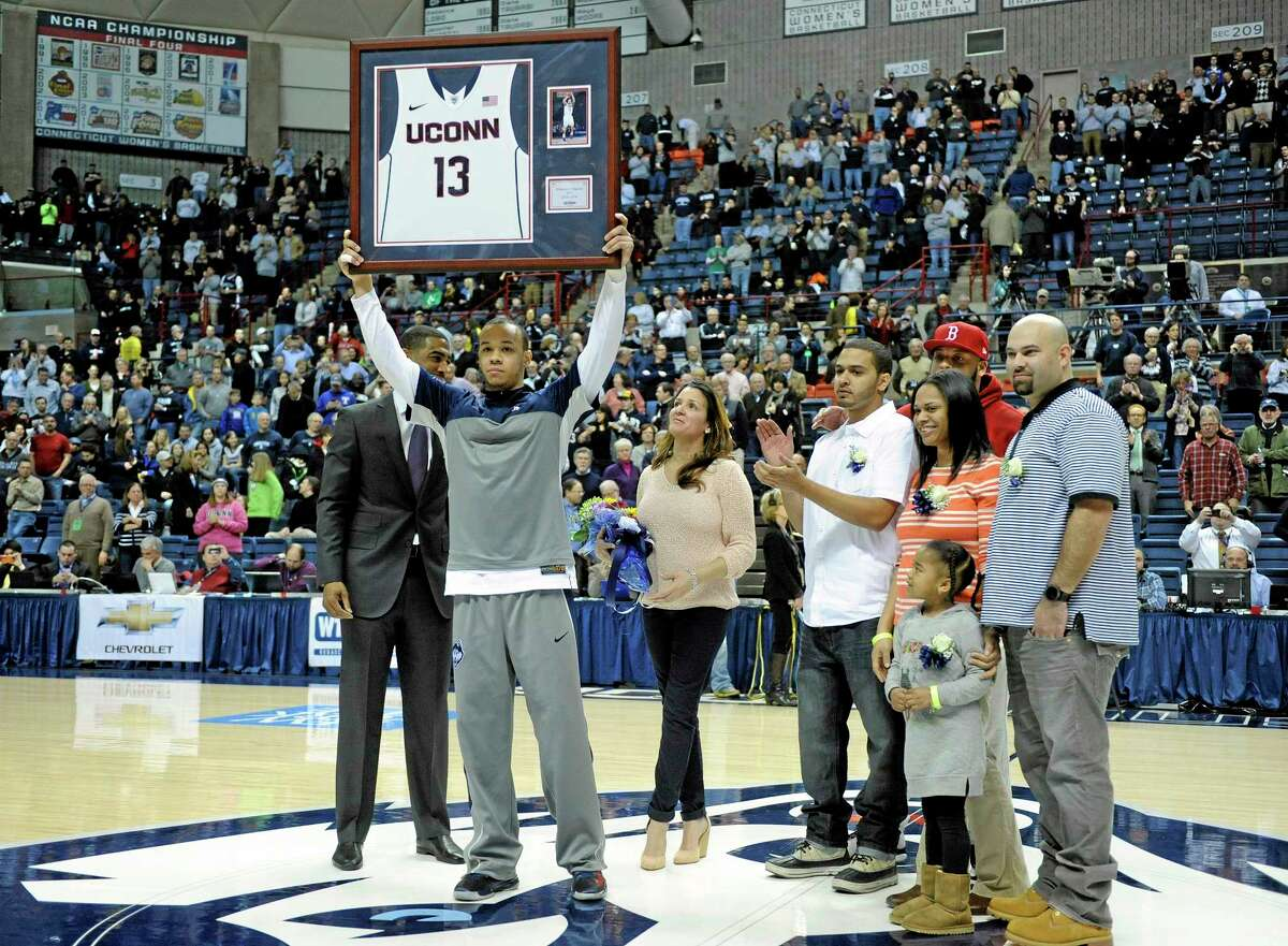 Shabazz Napier, joined by his family on Senior Night, holds up a plaque before No. 19 UConn's 69-63 win over Rutgers at Gampel Pavilion in Storrs on Wednesday.