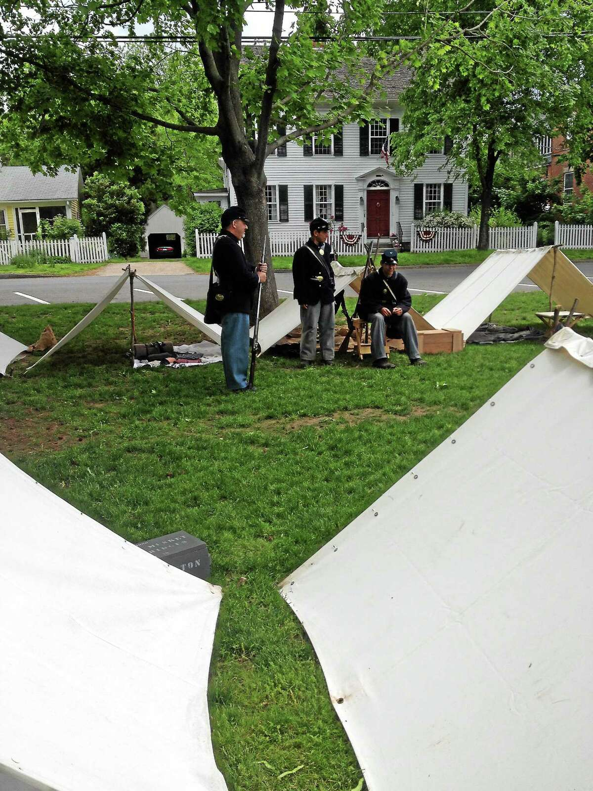 Civil War re-enactors from Company F Fourteenth Connecticut Volunteer Infantry sit at the encampment on the Guilford Green. Kristin Stoller - New Haven Register