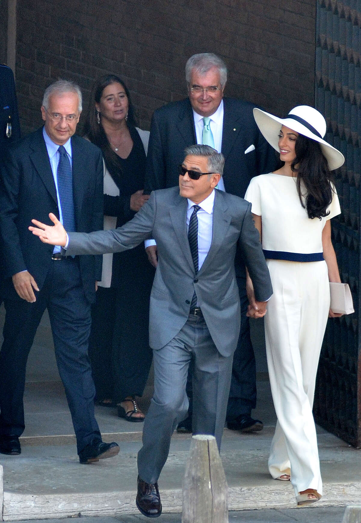 George Clooney and his wife Amal Alamuddin leave the city hall after their civil marriage ceremony performed by former Rome's mayor Walter Veltroni, left, in Venice, Italy, Monday, Sept. 29, 2014. George Clooney married human rights lawyer Amal Alamuddin Saturday, the actor's representative said, out of sight of pursuing paparazzi and adoring crowds. (AP Photo/Luigi Costantini)