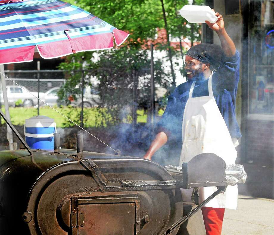 Gregory Martin, co-owner of the Caribbean Connection restaurant on Whalley Avenue in New Haven, cooks jerk chicken at his outdoor brazier. Photo: Mara Lavitt — New Haven Register    / Mara Lavitt