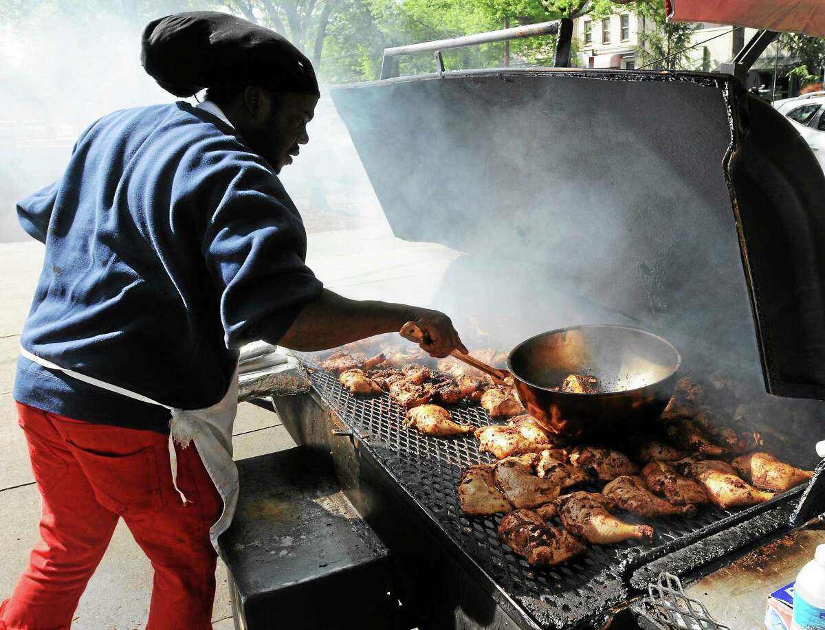 Gregory Martin, co-owner of the Caribbean Connection restaurant on Whalley Avenue in New Haven, cooks jerk chicken at his outdoor brazier.