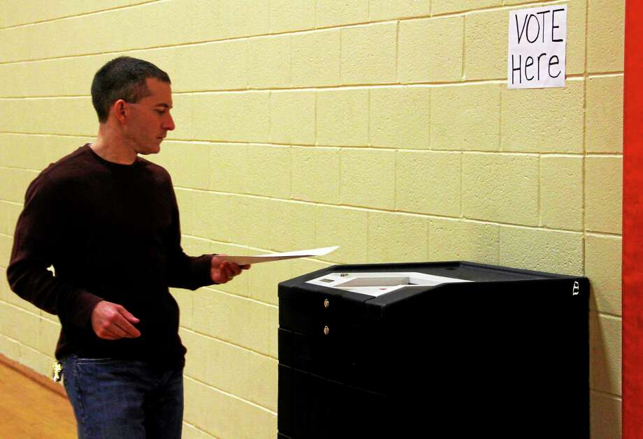 Ward Winegar casts his ballot on Saturday, May 31, 2014, during Winsted's budget referendum at Pearson School. Photo: Esteban L. Hernandez - The Register Citizen