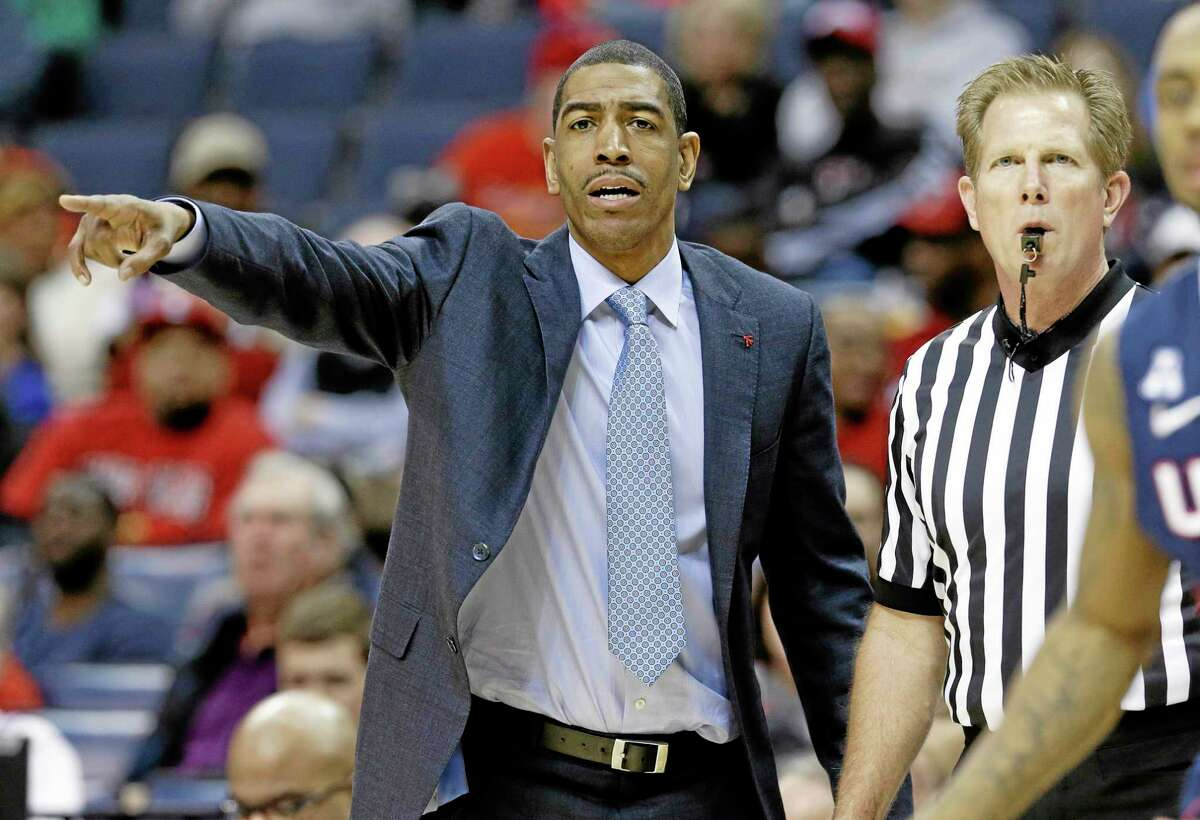 UConn coach Kevin Ollie gestures as he and an official watch during the second half of the Huskies' 58-56 win over Cincinnati in the semifinals of the American Athletic Conference tournament on Friday in Memphis, Tenn.