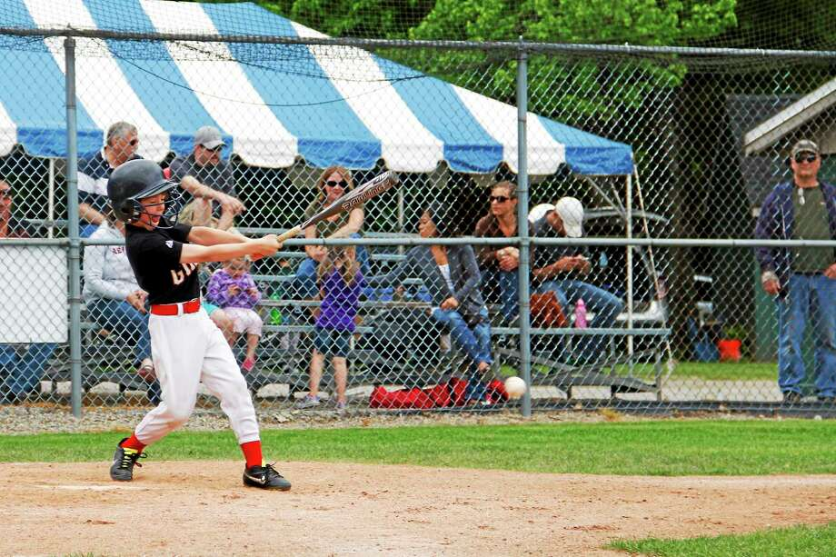 Connor Daigle, 7, of the New Hartford Giants, winces as he hits a ball on Saturday, May 31, 2014 during Vintage Day at Brown's Park in New Hartford. The event is a fundraiser for the New Hartford Youth Baseball/Softball league. Photo: Esteban L. Hernandez - The Register Citizen