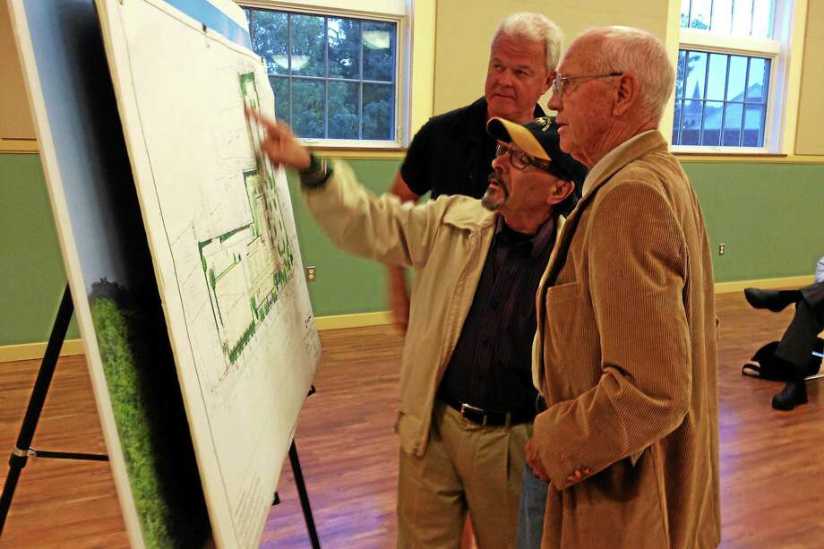 From left: Community members Jon Jensen, Egidio Recidivi and Chuck Perrett inspect a design schematic of the forthcoming Litchfield District Courthouse before a stakeholder's meeting Tuesday at Torrington City Hall. Photo: Esteban L. Hernandez — The Register Citizen