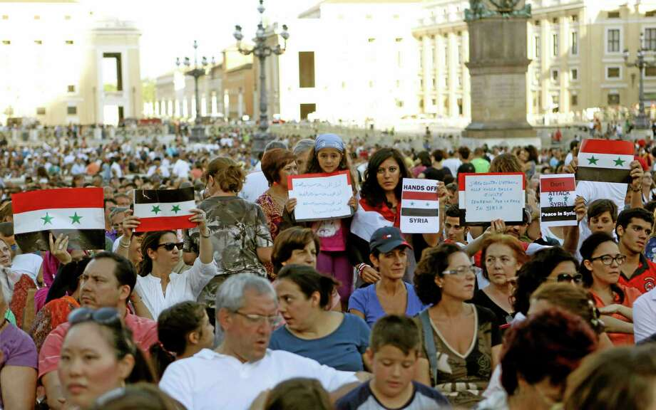 People hold Syrian flags and signs against a possible attack to Syria, prior to the start of a vigil for peace attended by Pope Francis in St. Peter's Square at the Vatican, Saturday, Sept. 7, 2013. Tens of thousands of people have answered Pope Francis' call and massed in St. Peter's Square for a 4-hour-long prayer vigil for peace in Syria. It was believed to be one of the first, and certainly the largest popular rally in the West against U.S.-led plans to strike Syria following the Aug. 21 chemical weapons attack near Damascus. (AP Photo/Riccardo De Luca) Photo: AP / AP