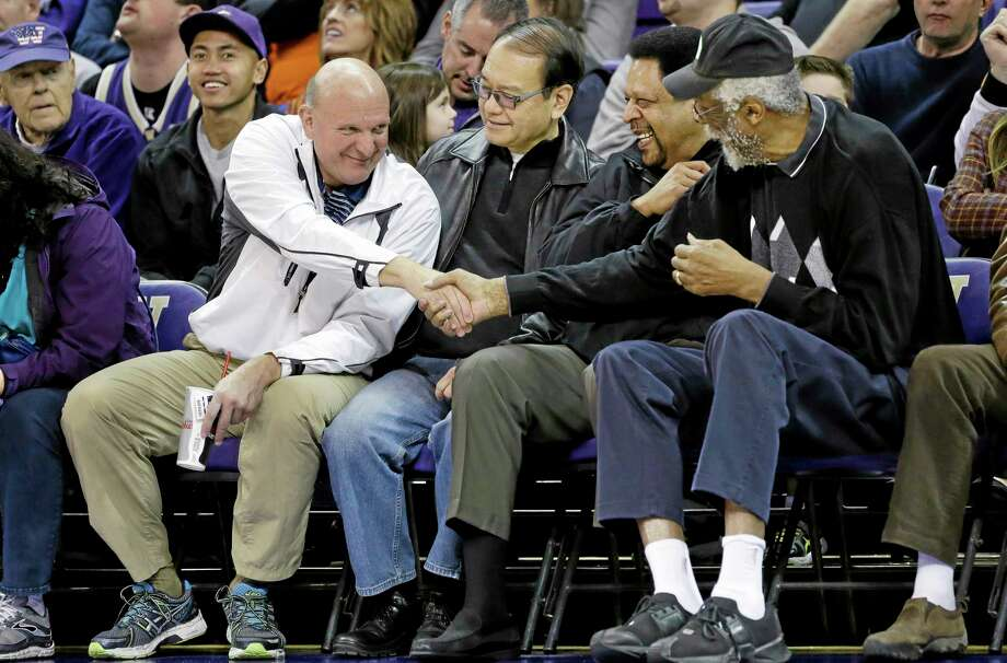 "In this Jan. 25 photo, then-Microsoft CEO Steve Ballmer, left, shakes hands with former NBA players Bill Russell, right, and ""Downtown"" Freddie Brown as Omar Lee looks on during a college basketball game between Washington and Oregon State in Seattle. Photo: Elaine Thompson — The Associated Press  / AP"