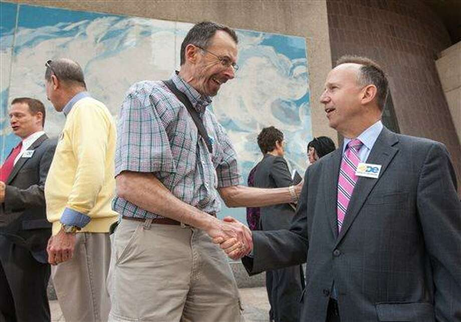 Ron Tipton, left, shakes Delaware Gov. Jack Markell's hand, thanking him for supporting same-sex marriage, Thursday afternoon, April 11, 2013, in Wilmington, Del. Tipton has been with his partner for 49 years. Delaware lawmakers introduced a bill Thursday that would legalize same-sex marriage in the state, with plans to have it signed into law by the end of June. (AP Photo/The News Journal, Kyle Grantham) Photo: AP / The News Journal