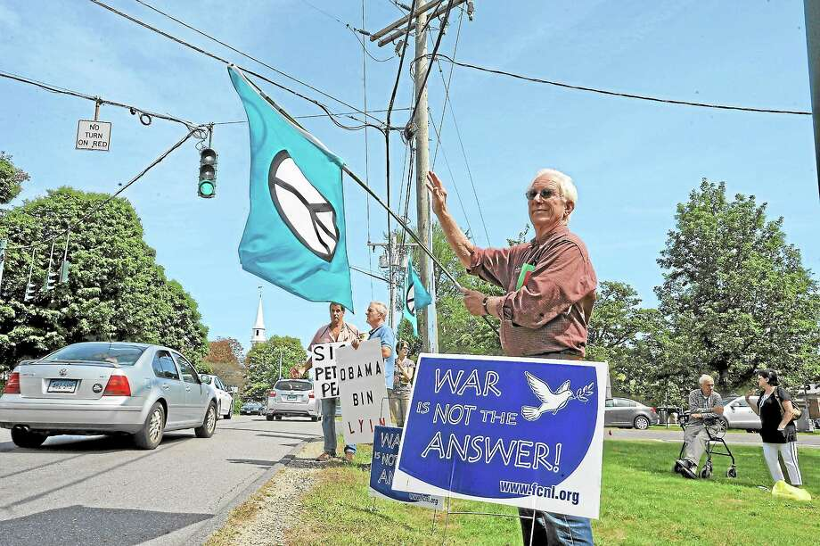 Peter Anderheggen of New Hartford waves a peace flag during a small protest of U.S. action against Syria on the Litchfield Green Saturday. Photo: Laurie Gaboardi—Register Citizen