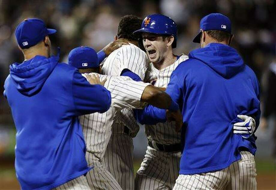 New York Mets' Mike Baxter, second from right, reacts as teammates mob him following his walk-off single during the 10th inning of the baseball game against the Chicago White Sox at Citi Field Tuesday, May 7, 2013 in New York. The Mets defeated the White Sox 1-0. (AP Photo/Seth Wenig) Photo: AP / AP
