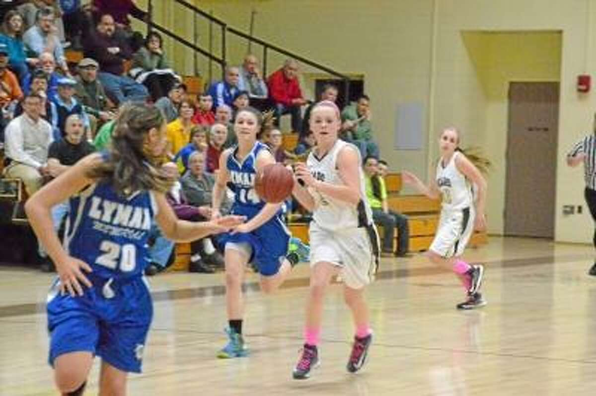 Thomaston's Abby Hurlbert dribbles down the court approaching Lyman Hall defenders. Photo by Pete Paguaga/Register Citizen