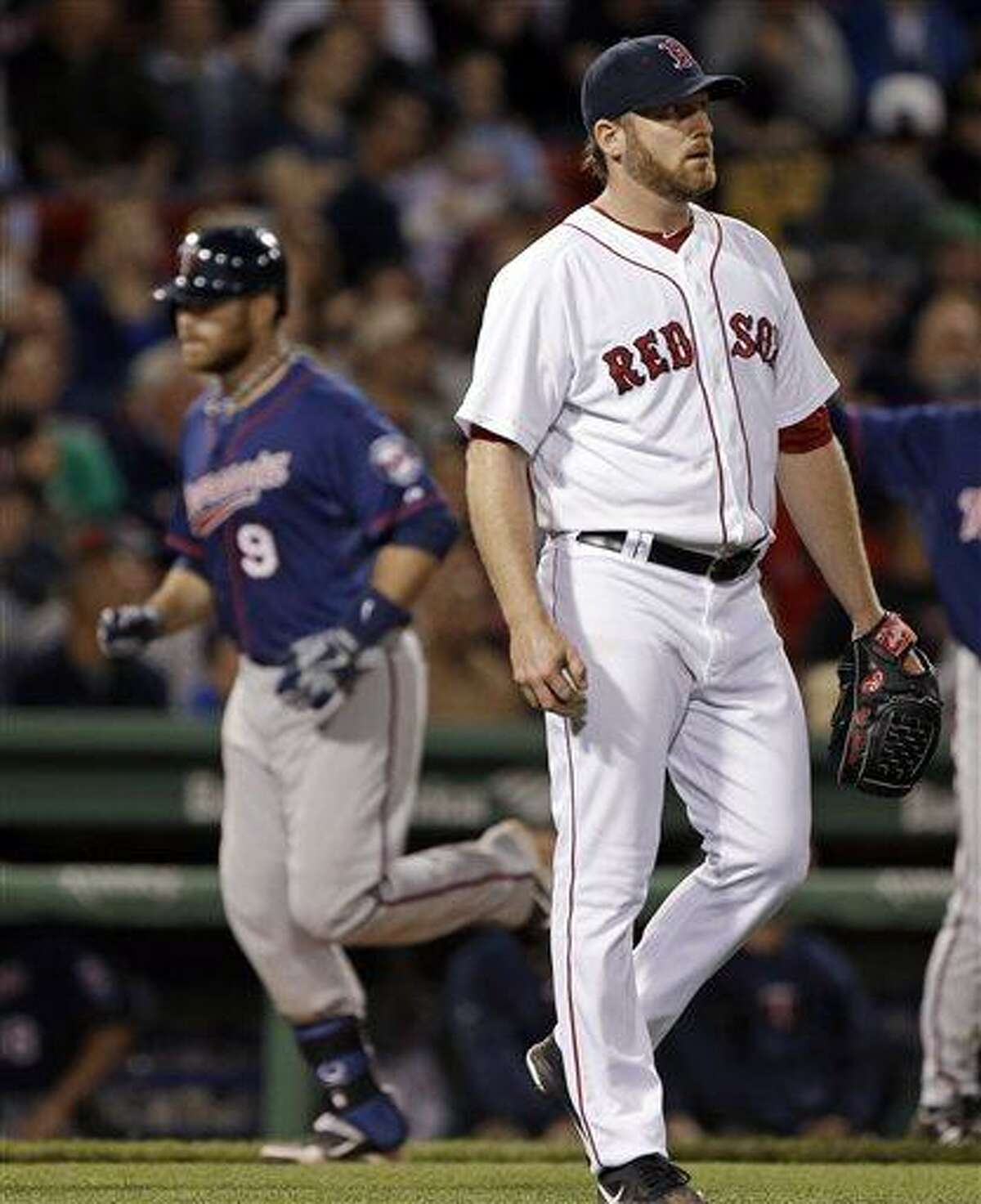 Boston Red Sox starting pitcher Ryan Dempster reacts as Minnesota Twins designated hitter Ryan Doumit (9) rounds third after hitting a solo home run during the seventh inning of a baseball game at Fenway Park in Boston, Tuesday, May 7, 2013. (AP Photo/Elise Amendola)