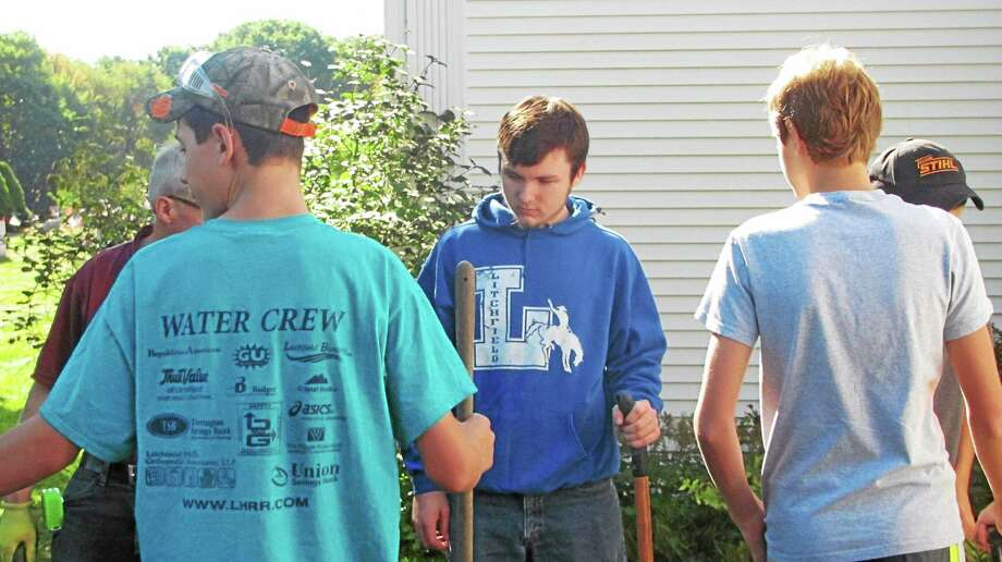 Litchfield High School senior Quinton Lautz, in blue sweatshirt, is building a perennial garden at Our Lady of Grace Church in Bantam as part of his Eagle Scout project. Photo: John Nestor — Special To The Register Citizen