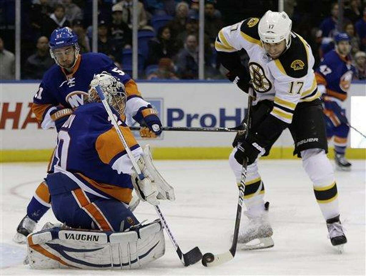 New York Islanders center Frans Nielsen of Finland (51) defends as Boston Bruins left wing Milan Lucic (17) tries to get a shot past New York Islanders goalie Evgeni Nabokov (20) of Kazakhstan in the first period of their NHL hockey game at Nassau Coliseum in Uniondale, N.Y., Tuesday, Feb. 26, 2013. The Hurricanes defeated the Islanders 4-2. (AP Photo/Kathy Willens)