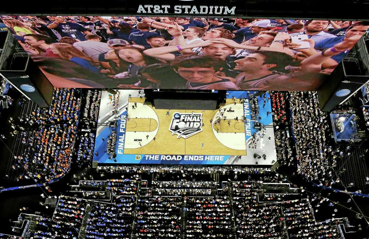 Connecticut fans are shown on the stadium scoreboard as they celebrate after the Huskies' 63-53 Final Four win over Florida on Saturday in Arlington, Texas.