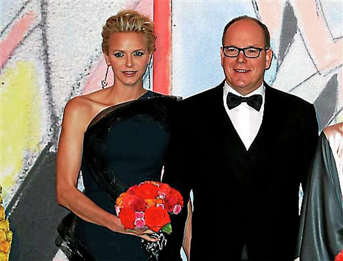 FILE- In this Saturday, March 29, 2014 file photo, Prince Albert II of Monaco, and his wife Princess Charlene pose for photographers as they arrive at the Rose Ball for the 50th anniversary of the Princess Grace Foundation, in Monaco. Princess Charlene of Monaco, who married Prince Albert II in 2011, has announced she is pregnant with the pair's first baby. The 36-year-old South African former Olympic swimmer and her husband issued a statement expressing their