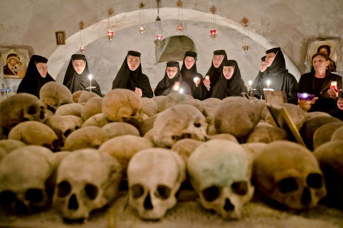 Romanian orthodox nuns sing in the ossuary at the Pasarea monastery, outside Bucharest, Romania, Sunday, May 5, 2013, during the Easter Religious service. The ossuary, containing mostly remains of the nuns that lived at the monastery is briefly opened on Easter night. (AP Photo/Vadim Ghirda)