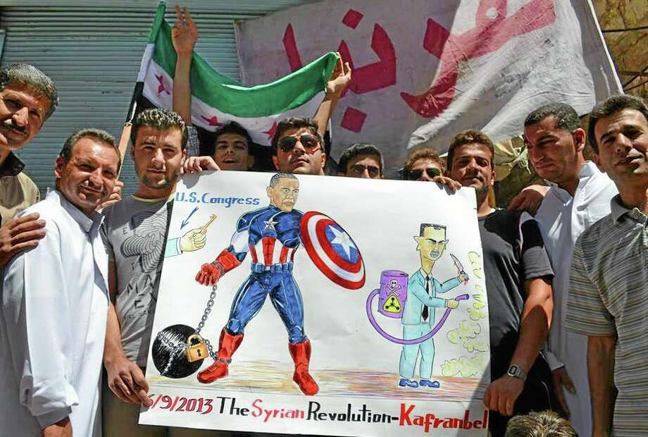 In this citizen journalism image provided by Edlib News Network, ENN, which has been authenticated based on its contents and other AP reporting, anti-Syrian regime protesters hold a poster depicting U.S. President Barack Obama and Syrian President Bashar Assad during a demonstration in Kafr Nabil town, Idlib province, northern Syria, Friday, Sept. 6, 2013. Obama is using his last day in Europe to renew his quest for foreign support for a U.S. military strike in Syria. But three days after he left Washington, it's unclear whether the global coalition the president has been seeking is any closer to becoming a reality. (AP Photo/Edlib News Network ENN) Photo: AP / EDLIB NEWS NETWORK ENN