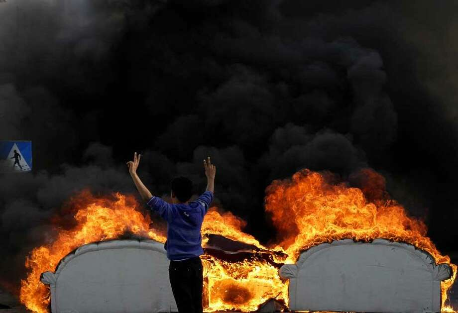 A Bahraini anti-government protester flashes the victory sign as he stands behind old furniture set on fire in a street in Malkiya, Bahrain, Tuesday, Feb. 26, 2013. Protests are being held in opposition villages nationwide, demanding the government release for burial the body of a 20-year-old who died last week from injuries sustained during earlier clashes with police. (AP Photo/Hasan Jamali) Photo: ASSOCIATED PRESS / AP2013