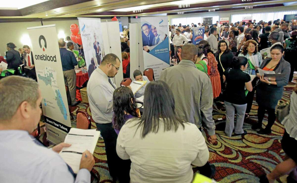 In this Wednesday, Aug. 14, 2013 photo, job seekers check out companies at a job fair in Miami Lakes, Fla. The Labor Department reports the number of Americans who applied for unemployment benefits for the first week of September on Thursday, Sept. 5, 2013. (AP Photo/Alan Diaz)