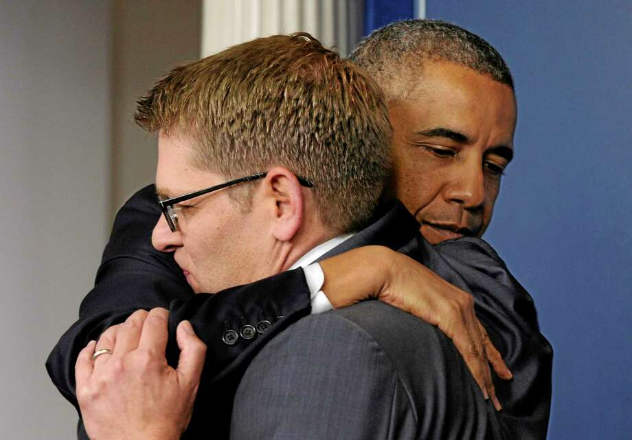 President Barack Obama gives White House press secretary Jay Carney a hug after announcing that Carney will step down later next month, during a surprise visit to the Brady Press Briefing Room of the White House, Friday, May 30, 2014. The president announced Carney's departure in a surprise appearance at in the White House press briefing room Friday. He said principal deputy press secretary Josh Earnest will take over the job. (AP Photo/Susan Walsh) Photo: AP / AP