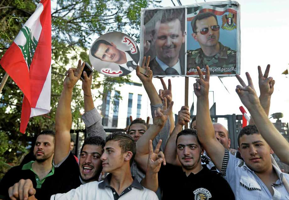 """Lebanese pro-Syrian regime supporters hold portraits of Syrian President Bashar Assad, as they flash victory signs during a demonstration against a possible military strike in Syria, near the U.S. Embassy in Aukar, east of Beirut, Lebanon, Friday, Sept. 6, 2013. The prospect of a U.S.-led strike against Syria has raised concerns of potential retaliation from the Assad regime or its allies. The State Department ordered nonessential U.S. diplomats to leave Lebanon over security concerns and urged private American citizens to depart as well. The portrait with Arabic words, left, reads:""""We are all with you."""" (AP Photo/Hussein Malla) Photo: AP / AP"""