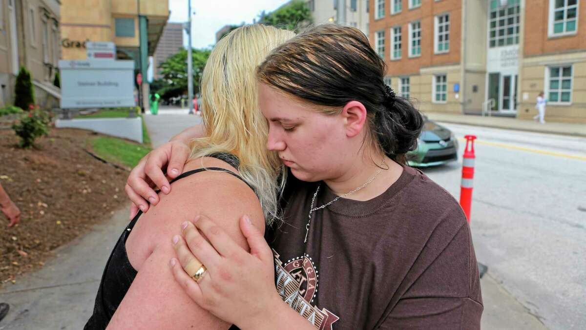 Alecia Phonesavanh, right, is hugged by her mother, Marlene Haygood, left, on Thursday, May 30, 2014 in Atlanta as they talk about an incident in which Phonesavanh's 19-month-old boy was critically injured when a police device was tossed into his bed Wednesday morning in Habersham County by a SWAT team in search of a drug suspect. Phonesavanh said there is no way officers should not have known they were children in the house. Habersham County Sheriff Joey Terrell said the officers were looking for a suspect who may have been armed and followed proper procedure by using the device. (AP Photo/Atlanta Journal-Constitution, John Spink)