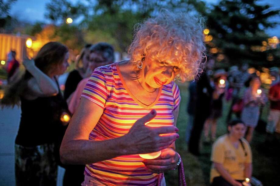 In this May 29, 2014 photo, Denee Mallon, center, participates in a candlelight vigil organized by Albuquerque Pride in Albuquerque, N.M. A U.S. Department of Health and Services review board ruled Friday, May 30, in favor of Mallon, a 74-year-old Army veteran, whose request to have Medicare pay for her genital reconstruction was denied two years ago. The decision recognizes sex reassignment surgeries as a medically necessary and effective treatment for individuals who do not identify with their biological sex. (AP Photo/Craig Fritz) Photo: AP / FR69896 AP