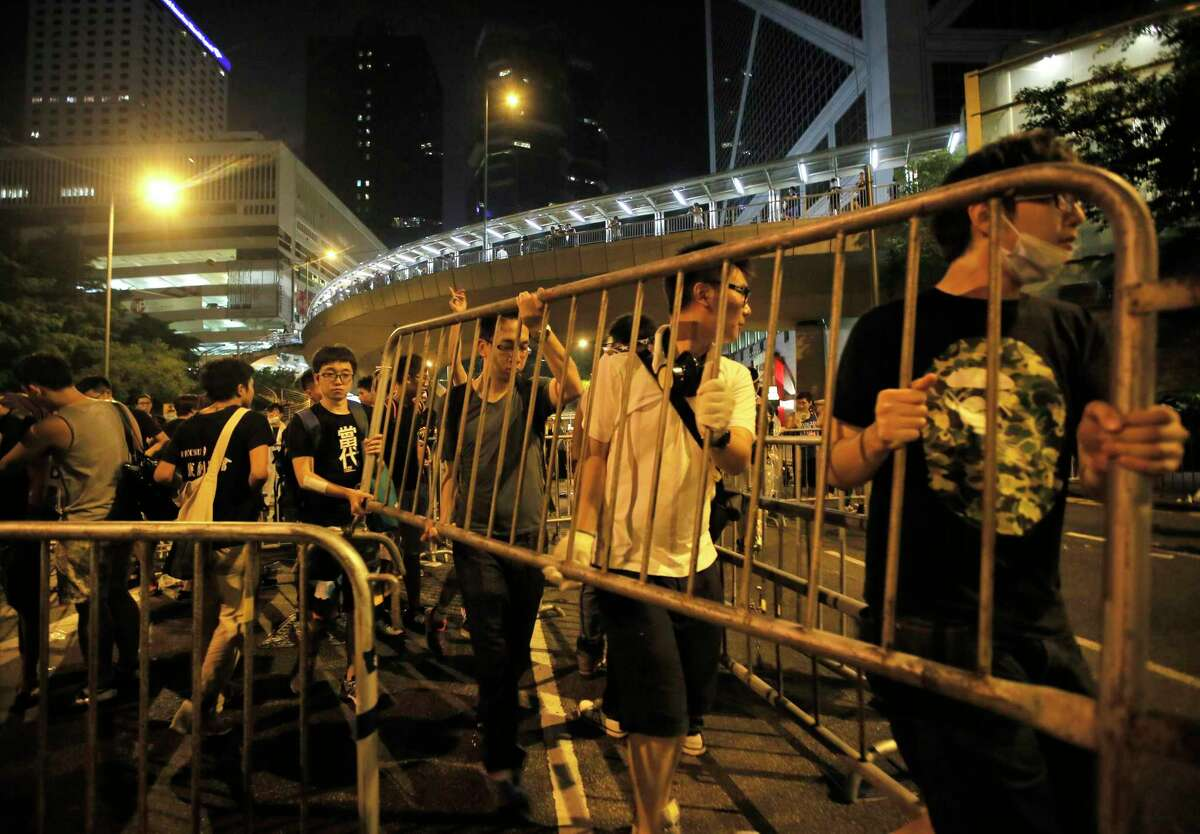 Student protesters fortify barricades to block main streets in the central business district of Hong Kong, late Monday, Sept. 29, 2014. Pro-democracy protesters expanded their rallies throughout Hong Kong on Monday, defying calls to disperse in a major pushback against Beijing's decision to limit democratic reforms in the Asian financial hub.