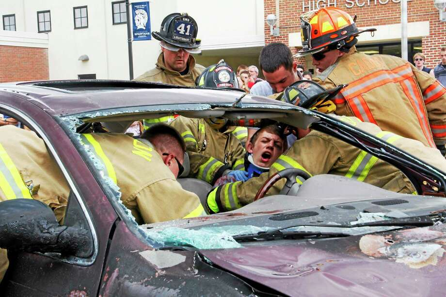 "An ""injured"" student is extracted from a car during a mock car accident on Friday, May 30, 2014, at Lewis Mills High School in Burlington. Esteban L. Hernandez Register Citizen Photo: Journal Register Co."