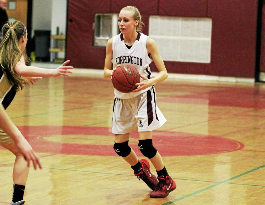 Torrington's Paige Middleton looks to make a pass during the Red Raiders 58-18 win over Woodland. Middleton finished with eight points. Photo: Marianne Killackey — Special To The Register Citizen  / 2013