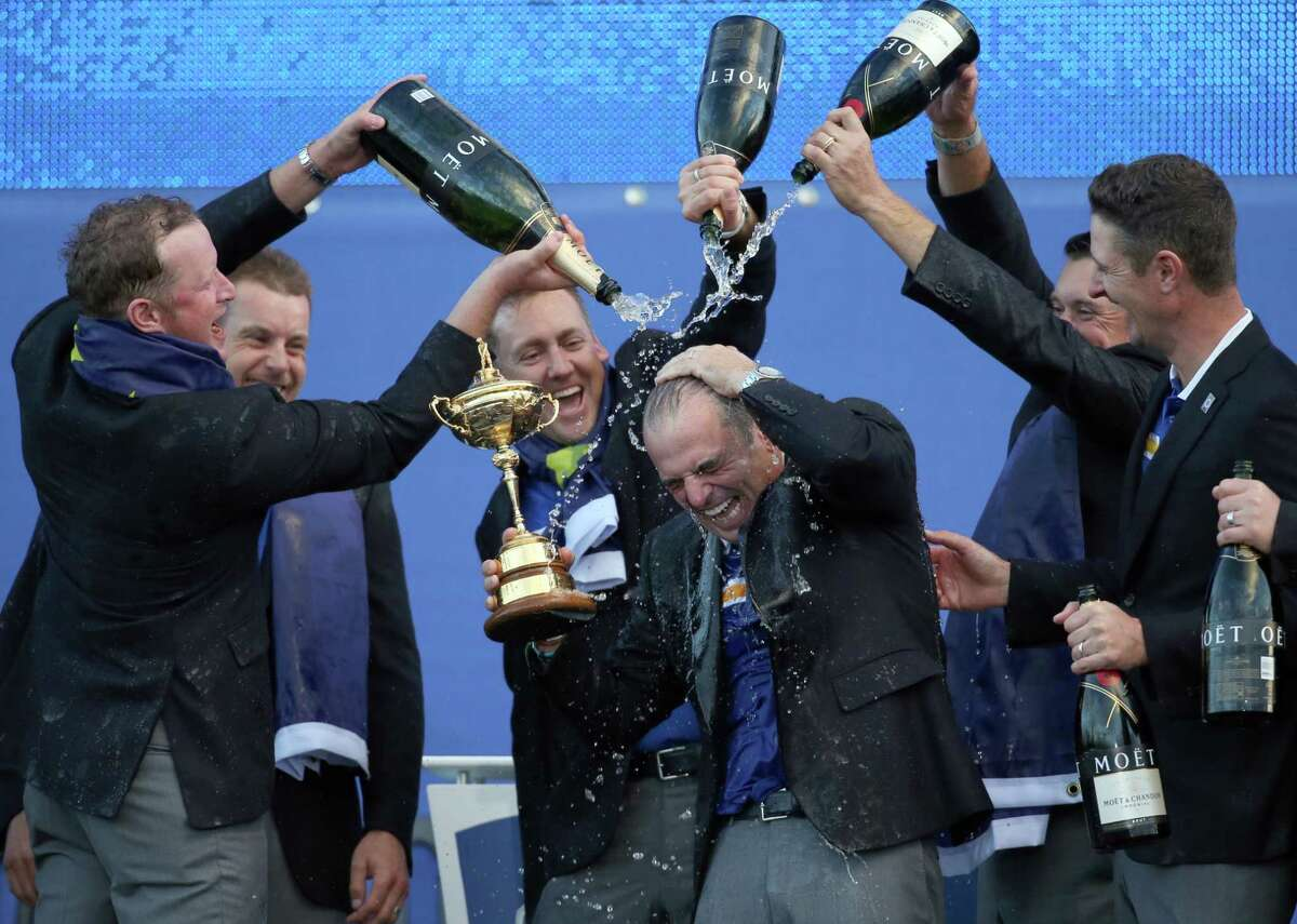From left, Europe's players Jamie Donaldson, Henrik Stenson, Ian Poulter, Lee Westwood and Justin Rose pour champagne over captain Paul McGinley as they celebrate winning the 2014 Ryder Cup.