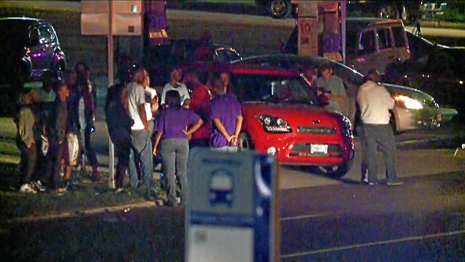 In this framegrab image courtesy of KSDK-TV a crowd gathers near the scene where a police officer was shot in the arm on Sept. 27, 2014 in Ferguson, Missouri. The officer was shot in the arm and is expected to survive, St. Louis County Police Chief Jon Belmar said. Photo: AP Photo/KSDK-TV  / KSDK-TV