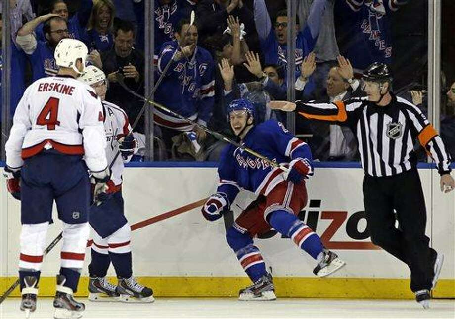 Washington Capitals defenseman John Erskine (4) watches as New York Rangers center Derek Stepan (21) reacts after scoring the winning goal in their 4-3 victory during the third period of Game 3 of their first-round NHL hockey Stanley Cup playoff series in New York, Monday, May 6, 2013. (AP Photo/Kathy Willens) Photo: AP / AP
