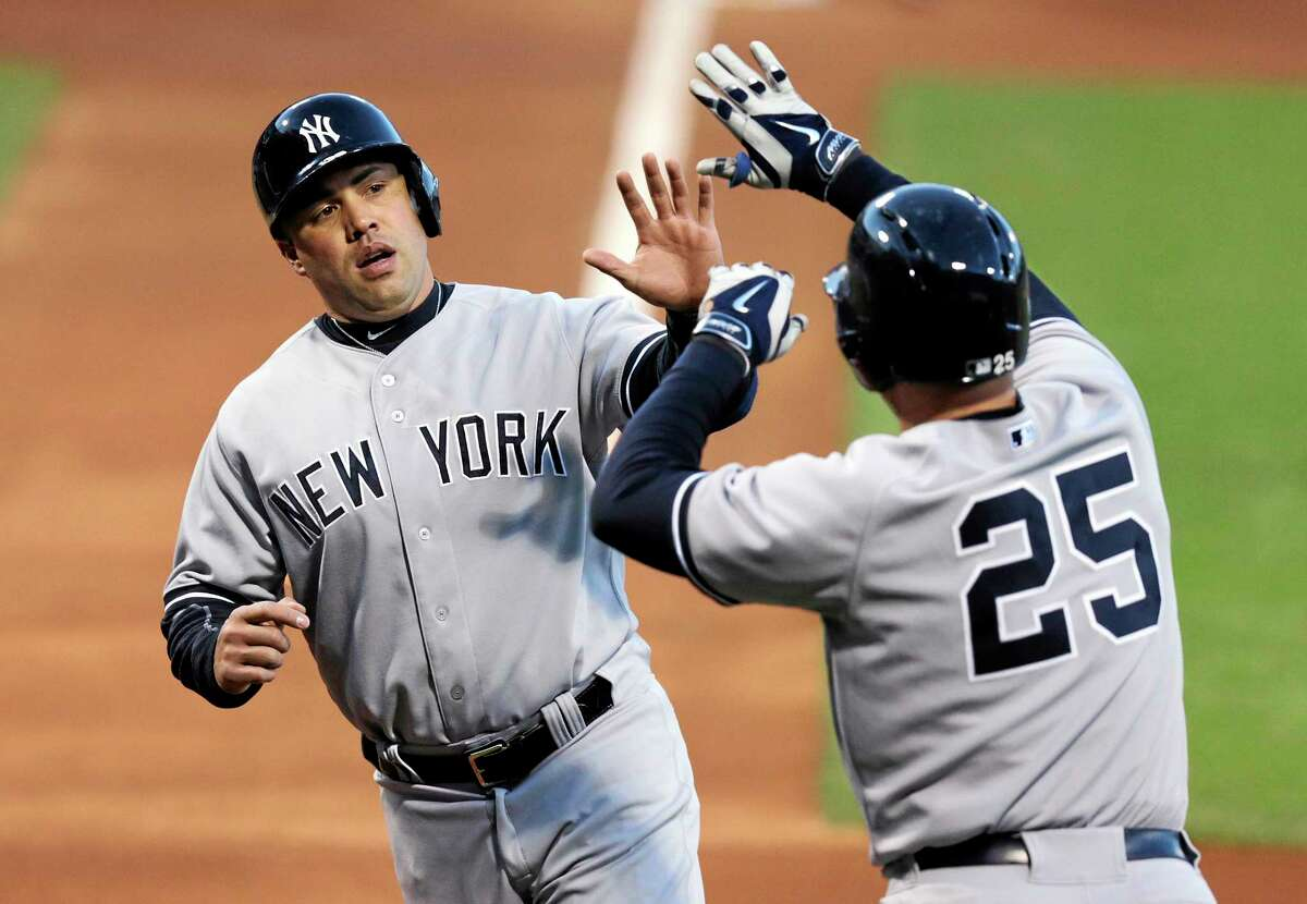 Yankees outfielder Carlos Beltran is congratulated by Mark Teixeira (25) after scoring a run during an April 24 game against the Red Sox in Boston.
