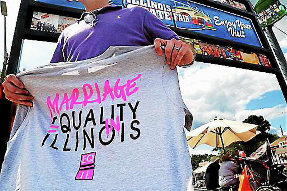 "In this Aug. 14, 2013 file photo, Randy Hannig of Equality Illinois, hands out shirts supporting gay marriage at the Illinois State Fair in Springfield, Ill. Minneapolis Mayor R.T. Rybak is hitting the road to promote his state's new gay marriage law. He is traveling to Chicago on Thursday, Sept. 5 to launch a ""Marry in Minneapolis"" campaign in the hopes that Illinois gay and lesbian couples will do just that. Illinois has not passed a gay marriage law, an issue is scheduled to come before state lawmakers again this fall. AP Photo/Stacy Bengs, Photo: AP / AP"