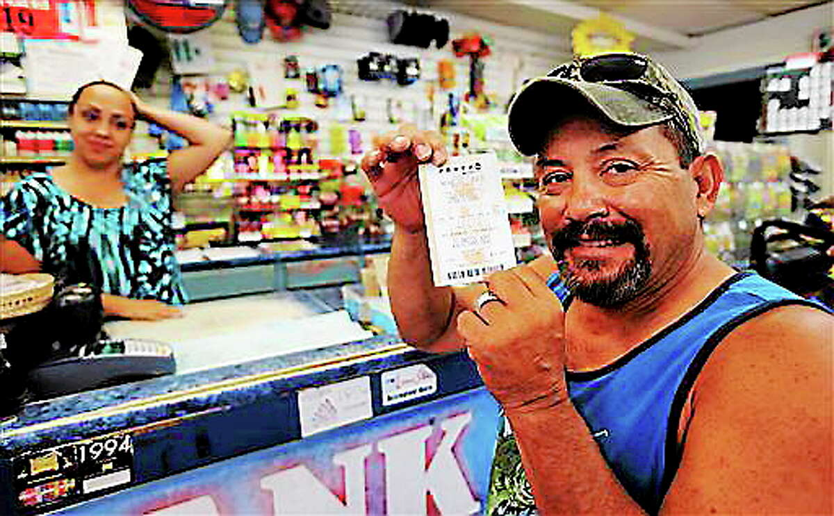 Tony Valdez, right, shows off his Powerball lottery ticket he purchased from Vanessa Sanchez, left, Wednesday, Aug. 7, 2013, in San Antonio. AP Photo/Eric Gay