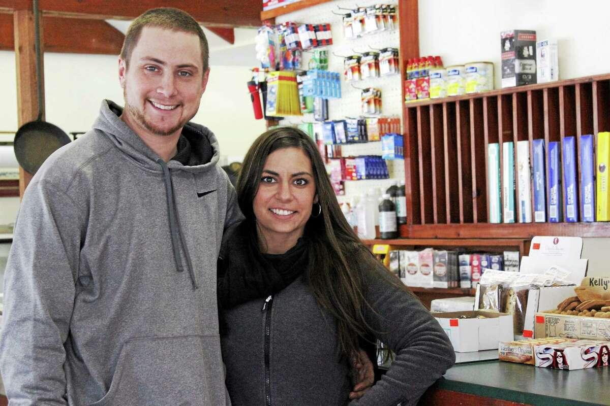 Ryan Craig and Natasha Travieso are busy preparing to open the store on Friday. (Shako Liu/The Register Citizen)